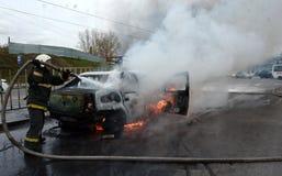 Strażacy gaszą płonącego samochód w Rosja Fotografia Royalty Free
