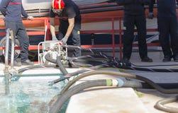 Strażacy pracuje z zasysającą pompą Zdjęcie Royalty Free
