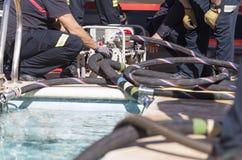 Strażacy pracuje z zasysającą pompą Zdjęcie Stock