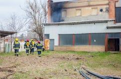 Strażacy są nadzorują płonącego przemysłowego budynek, przygotowywającego dla fotografia stock