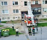 Strażacy w akci, dwa one dostają aboard w teleskopowego huku kosz Dwa funkcjonariuszów policji stojak obok samochodu strażackiego Zdjęcia Royalty Free
