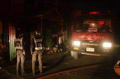Strażacy z samochodem strażackim iść pożarniczy hydrant przy domem byli dalej Zdjęcie Stock