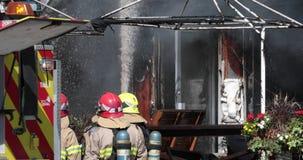 Strażak kiści woda na ścianie z wężem elastycznym na pożarniczym budynku zdjęcie wideo