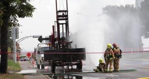 Strażak kiści woda na benzynowym przecieku zbiory