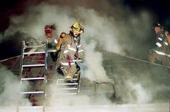 Strażak na dachu płonący domowy obramowany w dymu zdjęcie royalty free