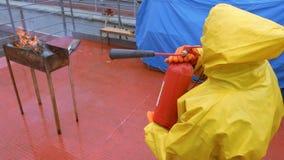 Strażak w żółtym deszczowu gasi ogienia w grillu pożarniczy gasidło zbiory wideo