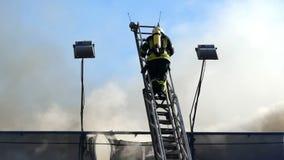 Strażak wspina się wysokiego kruszcowego schody z rozwidleniami płomień pod on zdjęcie wideo