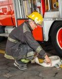 Strażaka przycupnięcie Podczas gdy Trzymający węża elastycznego Przy ogieniem Obrazy Stock