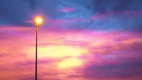 Stra?enlaterne, das das Sonnenunterganglicht und schwarzen die Regenwolken belichtet, die sich schnell ?ber den Himmel bewegen stock footage