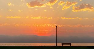 Stra?enlaterne und Bank vor dem sch?nen hellen roten Sonnenuntergang lizenzfreie stockbilder