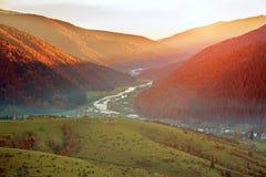 Stra?enwanderweg in den bunten Bergen des Herbstes auf Hintergrund des Tales und des ausgezeichneten Sonnenunterganghimmels stockbilder