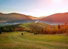 Stra?enwanderweg in den bunten Bergen des Herbstes auf Hintergrund des Tales und des ausgezeichneten Sonnenunterganghimmels lizenzfreies stockbild