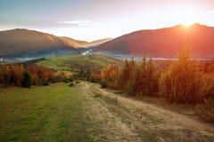 Stra?enwanderweg in den bunten Bergen des Herbstes auf Hintergrund des Tales und des ausgezeichneten Sonnenunterganghimmels stockfoto