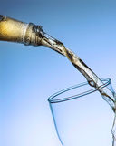 Straal van bier van de fles in het glas op de blauwe achtergrond Royalty-vrije Stock Foto's