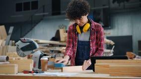 Straal van het vrouwelijke werknemer de oppoetsende hout in houten workshop die hand schurend blok gebruiken stock videobeelden