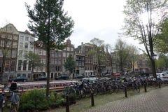 Straat in Amsterdam met heel wat fietsen, auto's en boten stock afbeelding
