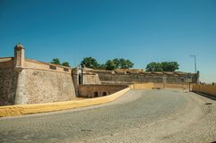 Straat bij de stadsmuur met een ingang en een kleine brug stock foto's