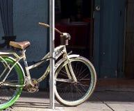 Straat met een oude die fiets aan een pool wordt geketend stock foto