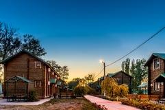 Straat met houten plattelandshuisjes in de avond na zonsondergang met verlichting royalty-vrije stock foto's