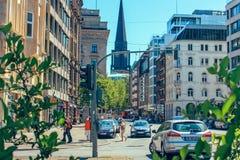 Straat met mensen en auto's dichtbij metro post Alsterhaus en meer Alster Binnenalster Hamburg, Duitsland stock afbeelding