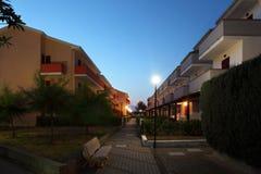 Straat tussen plattelandshuisjes in avond Royalty-vrije Stock Afbeeldingen