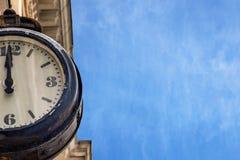 Straat uitstekende klok op een oud gebouw tegen een blauwe hemel met luchtwolken royalty-vrije stock foto
