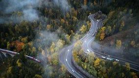 Straat van bovengenoemde trog een nevelig bos die bij herfst, luchtmening door de wolken met mist de vliegen en bomen royalty-vrije stock foto's