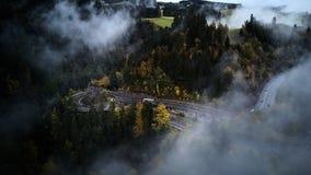Straat van bovengenoemde trog een nevelig bos die bij herfst, luchtmening door de wolken met mist de vliegen en bomen Royalty-vrije Stock Afbeelding