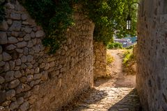 Straat van oude stad met zonlicht op steenboog stock foto's