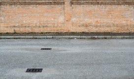Straatachtergrond in de voorsteden voor exemplaarruimte Asfaltweg met mangaten voor een stoep met onkruid en een brickwall royalty-vrije stock fotografie