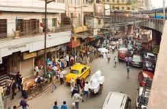 Straatbeweging met auto's, handelaarkarretjes en menigte van mensen in reusachtige Aziatische stad Royalty-vrije Stock Fotografie