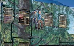 Straatkunst van twee jongens die op boom in Frankston, Australië zitten stock foto