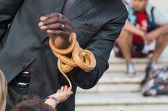 Straatkunstenaar het spelen met een slang voor jonge geitjes Stock Foto's