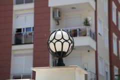 Straatlantaarn in de vorm van een bal in het gesmede kader in de de zomerzon Stock Foto