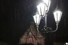 Straatlantaarn die in de duisternis bij een regenachtige nacht glanzen stock afbeelding