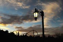 Straatlantaarn en een achtbaansilhouet op de achtergrond royalty-vrije stock afbeelding