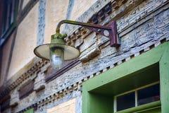 Straatlantaarn het hangen boven oude deur bij uitstekend huis Stock Afbeeldingen