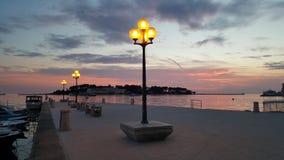 Straatlantaarns door het overzees bij zonsondergang stock foto's
