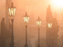 Straatlantaarns op Charles-brug door zon in de ochtend wordt verlicht, Oude Stad, Praag, Tsjechische Republiek die stock afbeelding