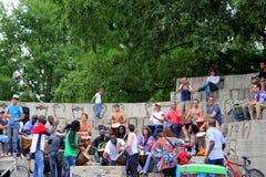 Straatmusici met hun families en kinderen bij het openbare park van stad stock fotografie