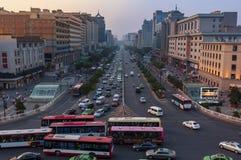 Straatscène in de stad van Xian bij zonsondergang, met een weg en een opstopping, in China Stock Foto