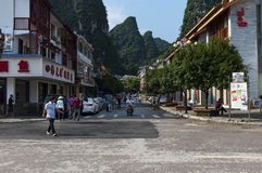 Straatscène in de stad van Yangshuo met mensen in een straat en de lange kalksteenpieken op de achtergrond, in China Stock Afbeeldingen