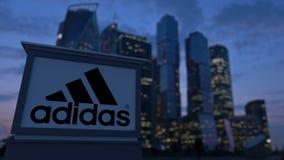 Straatsignage raad met Adidas-inschrijving en embleem in de avond Vage bedrijfsdistrictswolkenkrabbers backgroun Royalty-vrije Stock Foto's