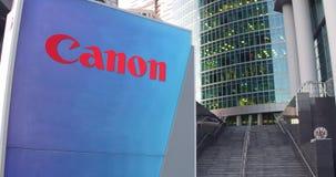 Straatsignage raad met Canon Inc embleem De moderne wolkenkrabber van het bureaucentrum en tredenachtergrond Het redactie 3D teru Royalty-vrije Stock Afbeeldingen