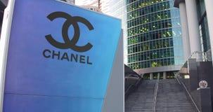 Straatsignage raad met Chanel-embleem De moderne wolkenkrabber van het bureaucentrum en tredenachtergrond Het redactie 3D terugge Royalty-vrije Stock Afbeelding