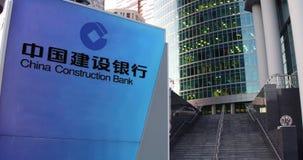 Straatsignage raad met China Construction Bank-embleem De moderne wolkenkrabber van het bureaucentrum en tredenachtergrond redact stock illustratie