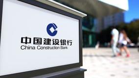 Straatsignage raad met China Construction Bank-embleem Vage bureaucentrum en het lopen mensenachtergrond redactie stock illustratie
