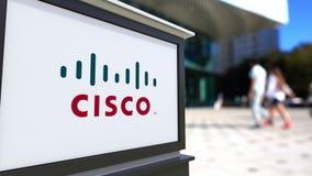 Straatsignage raad met Cisco Systems-embleem Vage bureaucentrum en het lopen mensenachtergrond Redactie 3D Royalty-vrije Stock Afbeeldingen