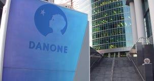 Straatsignage raad met Danone-embleem De moderne wolkenkrabber van het bureaucentrum en tredenachtergrond Het redactie 3D terugge Royalty-vrije Stock Afbeeldingen