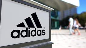Straatsignage raad met de inschrijving en het embleem van Adidas Vage bureaucentrum en het lopen mensenachtergrond Redactie 3D Royalty-vrije Stock Fotografie